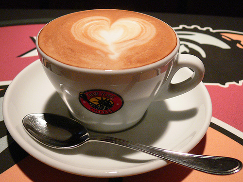 Cup of coffee with heart shaped swirl of cream