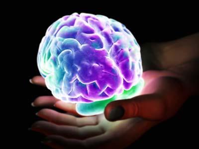 Glowing brain held by hands