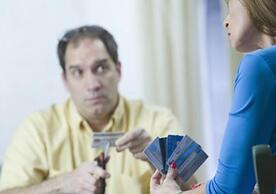 Man cutting credit cards, woman holding more credit cards.